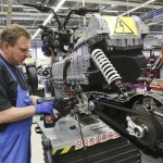 A mechanic assembles a BMW C evolution electric maxi-scooter at the BMW motorcycle plant in Berlin